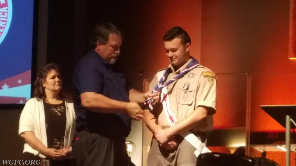 Chris's father replaces the neckerchief with that of an Eagle Scout.